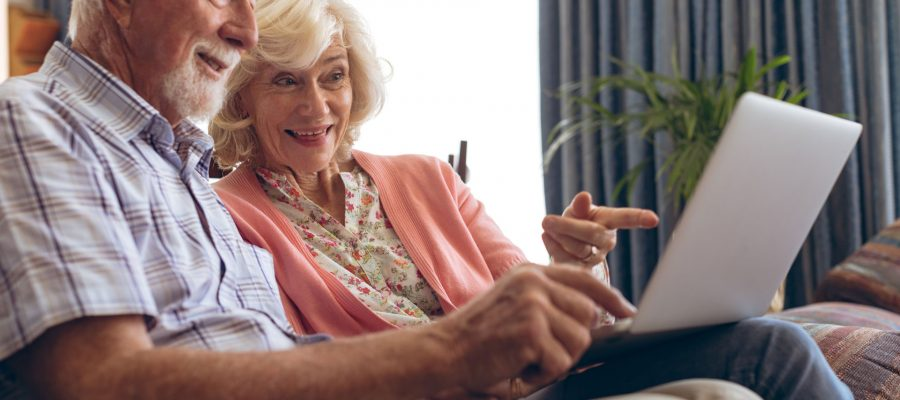 Side view of senior Caucasian couple interacting with each other while using laptop at retirement home. Couple sits on sofa while pointing with their fingers towards the screen of the laptop.